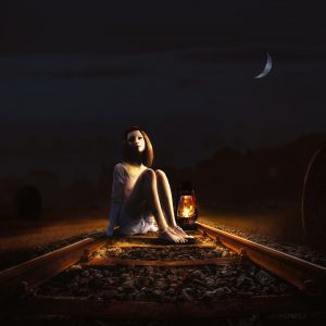 A woman on the train tracks in the dark, with a lantern